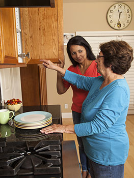 Woman getting dishes from cupboard with younger woman helping.