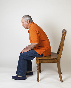 Man sitting at front edge of chair, getting ready to stand up.