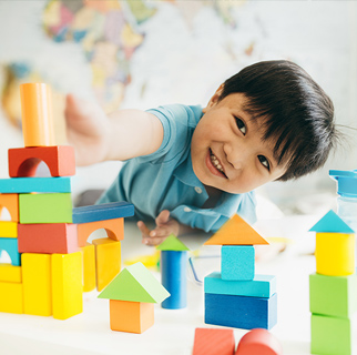 Preschool child playing on the floor with blocks.