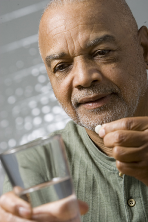 Man holding glass of water, preparing to take pill.