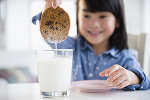 Girl dunking cookie in milk.